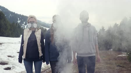 three young men stand in gas masks bad air and smoke
