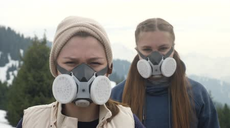 two young girls in a gas mask in the smoke. Close-up