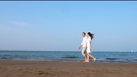 Happy romantic couple walking down the beach at sunset Wideo