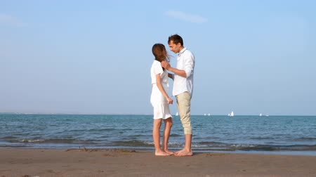 Young Couple kissing together on the sunny beach