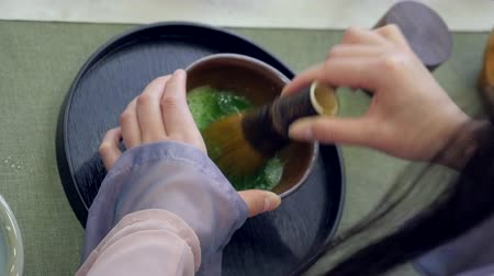Making process Matcha green tea, traditional japanese style, bamboo whisk
