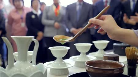 Chinese tea ceremony performance. Pours tea into a cup. People on the background