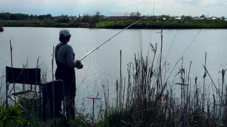 Silhouette of woman fishing and throwing the Fishing Rod in a lake. Back view. Wideo