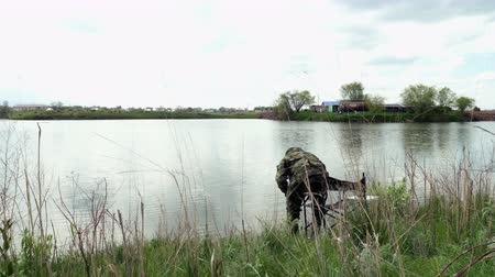 Long shot of Fishing Man in camouflage sitting on chair with hat in a cloudy day