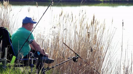 Side view. Fisherman sits on a chair on the bushy grass shore lake and fishing Wideo