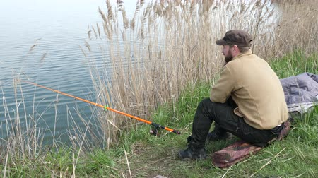 bushy : Fisherman sits and fishes on the shore. Man waiting a fish with a fishing rod.