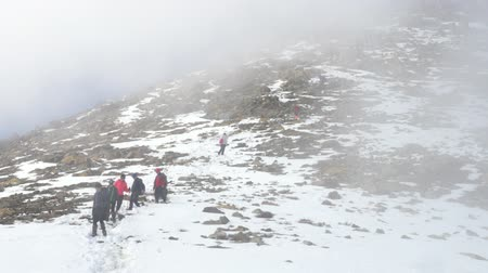 A group of climbers descent from the mountains in winter. Cloudy