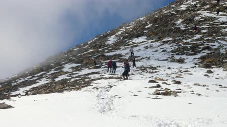 reaching : group of tourists team returns from a difficult trek to the mountains in winter