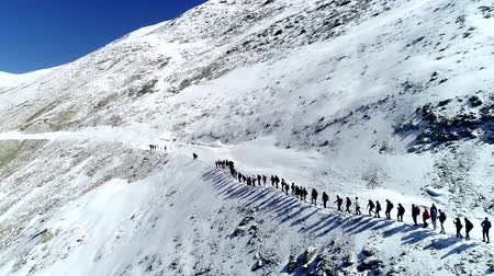 climbers group in chain goes up snowy mountain slope to top. Drone aerial shot