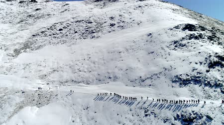 Big team of tourists climb up in one row in winter snow mountains. Aerial. Drone