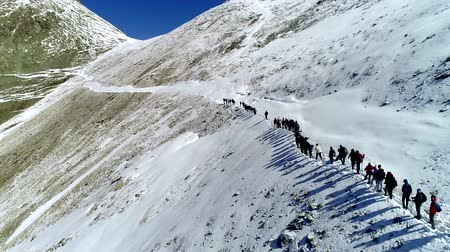 Aerial view from behind. Group of climbers climbing a mountain in winter. Wideo