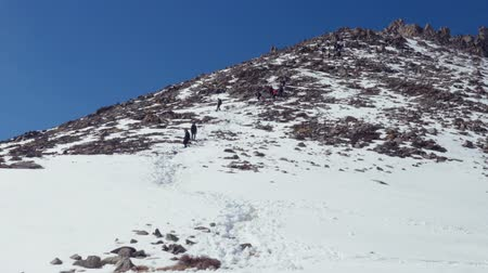 tired climbers descend from a rocky mountain along snow-covered path. Winter day