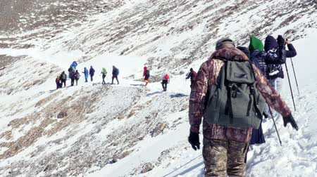 teamwork tourists go on snow in winter climbing top mountains rocks peak team