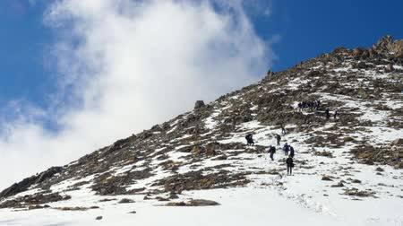 hard difficult descent from a mountain. Group of climbers go down from snow hill Vídeos