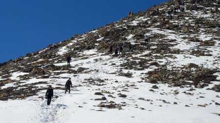 Tired group of climbers descent from the snow mountain in winter day. Long shoot