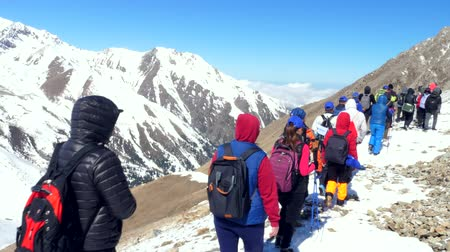 ulaşmak : climbers in colored clothes go in a row along the snowy mountains. Sunny day