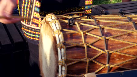 percussão : Djembe drumming in slow motion. Wooden african drum. Close up