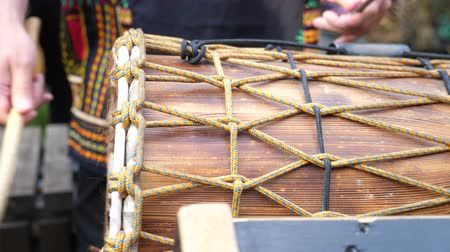 Close up drum up of hands drumming out a beat on African skin covered djembe