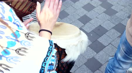 kmenový : close-up of female hands playing the djembe jembe drum in slow motion on street