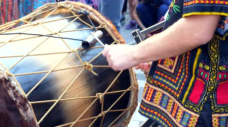 Man playing at djembe drums with drumsticks outdoor in slow motion