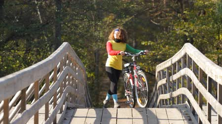 bisiklete binme : girl goes by bicycle on a bridge