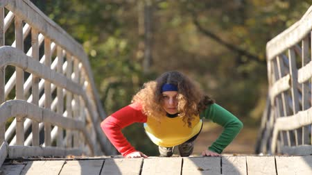 atleta : caucasian girl doing push ups on a bridge Stock Footage