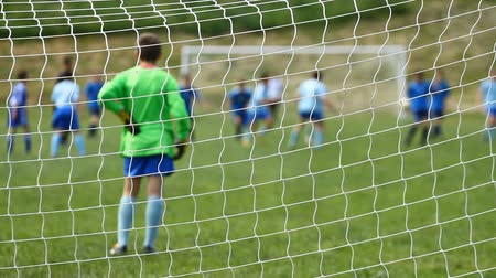 eğlence oyunları : Children soccer game from behind goal net Stok Video