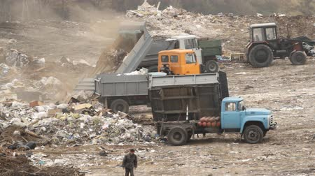 doldurmak : Garbage trucks unload garbage on a dump