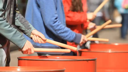 zapasy : People playing on metal barrels with the drum sticks