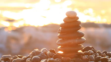 шуй : Pyramid of pebbles with sunrise on the sea splashes Стоковые видеозаписи