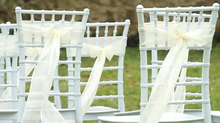 lakodalom : White wedding chairs with silk ribbons Stock mozgókép