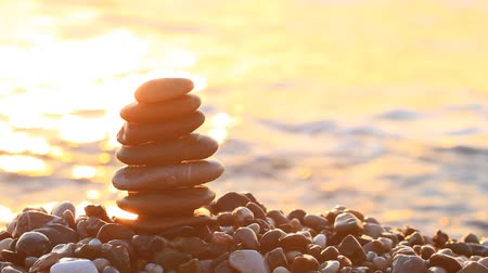 shui : Pyramid of pebbles at sunrise on the sea.