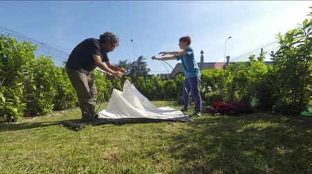 sátor : Couple setting up a tent camp in the home garden. Timelapse.