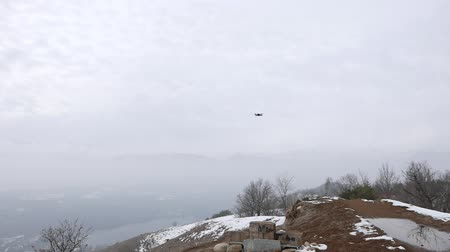 szakértő : Drone flying in the mountains, cloud weather, snow. People playing with drone quadcopter for filming purpose.