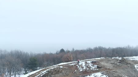функция : Aerial drone: couple playing with drone on mountain ridge with fog and snow, mistic forest Стоковые видеозаписи