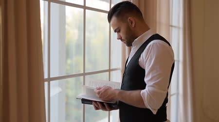 believer : A young man standing near window and flips through a book.