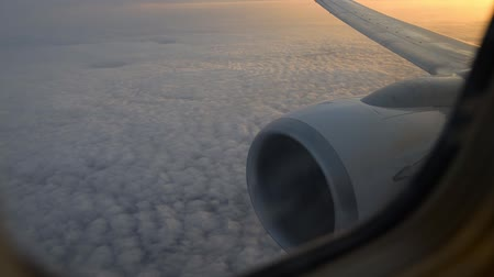 aeroespaço : View of airplane wing through plane window. Flying above the clouds at sunrise.