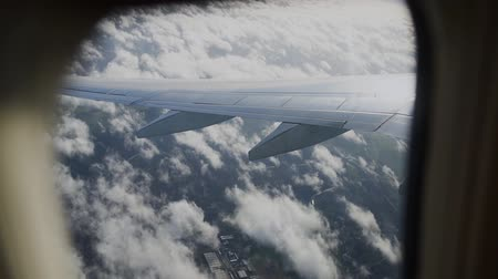 aeroespaço : View of airplane wing through plane window. Flying above the clouds.