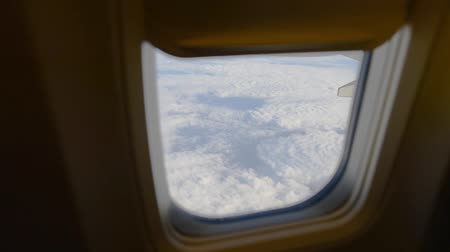 pólen : View of airplane wing through plane window. Flying above the clouds.
