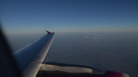 advert : View of flying airplane wing through plane window.