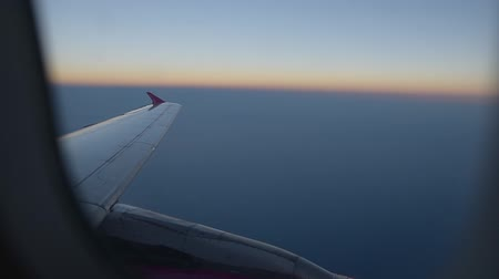 open sky : View of flying airplane wing through plane window.