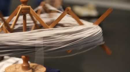 wooden spinning wheel that turns into a skein of wool for the artisan tailoring Stok Video