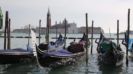 Many gondolas to the tourists in Venice near Saint Mark Square and the Church of Saint George in the background
