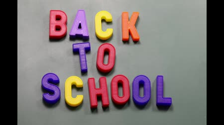 colored magnetic letters with BACK TO SCHOOL text jerky on the blackboard