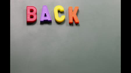 magnetic letters on the blackboard forming the text BACK TO SCHOOL Stok Video