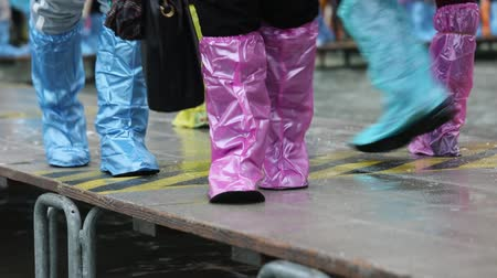 People with plastic leggings during the flood in Venice
