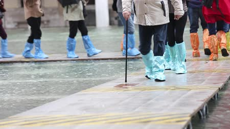 People with plastic gaiters during the flood in Venice