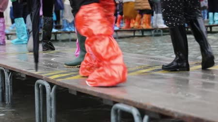 People with gaiters during the flood in Venice Stok Video