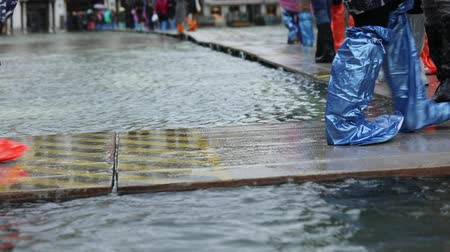 People with plastic gaiters or boots during the high tide in Venice