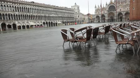 Chairs and tables in Saint Marks square during the Tide in Venice
